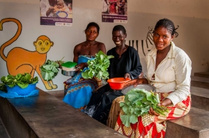 Three women hold up the fresh greens from the first harvest