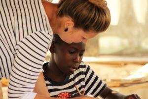 Melanie (volunteer) helps Winstoni write his story.