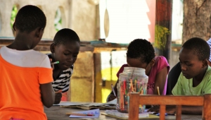 Children drawing and writing around the table.