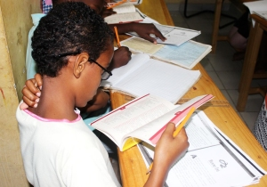 Children reading textbooks and writing in notebooks at desks.