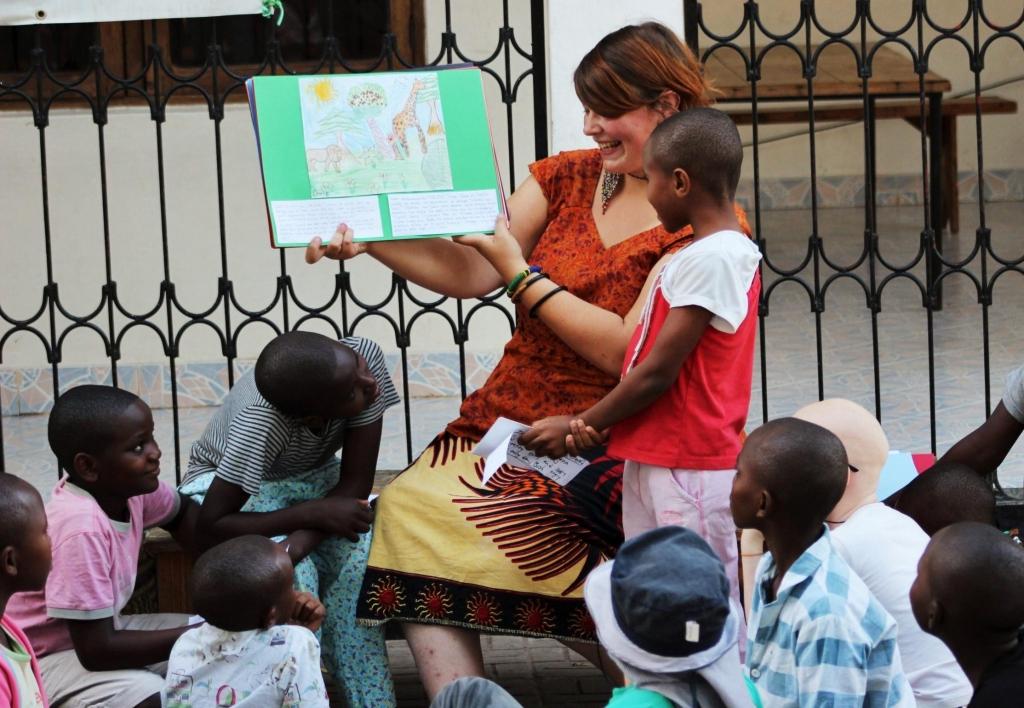Children watch as volunteer presents the storybook.
