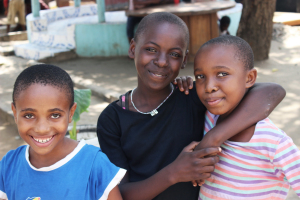 Three Children's Home girls smiling for camera