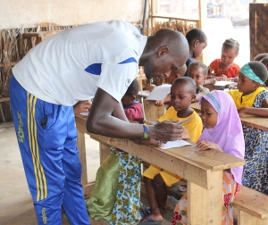 Moses, our local volunteer, aids a student in her handwriting